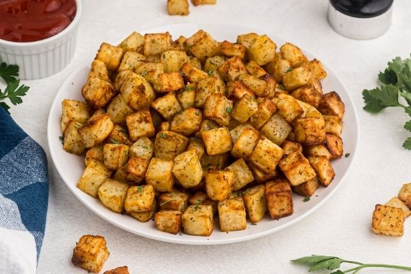 Golden cubed potatoes cooked and served on a white plate with parsley and ketchup.