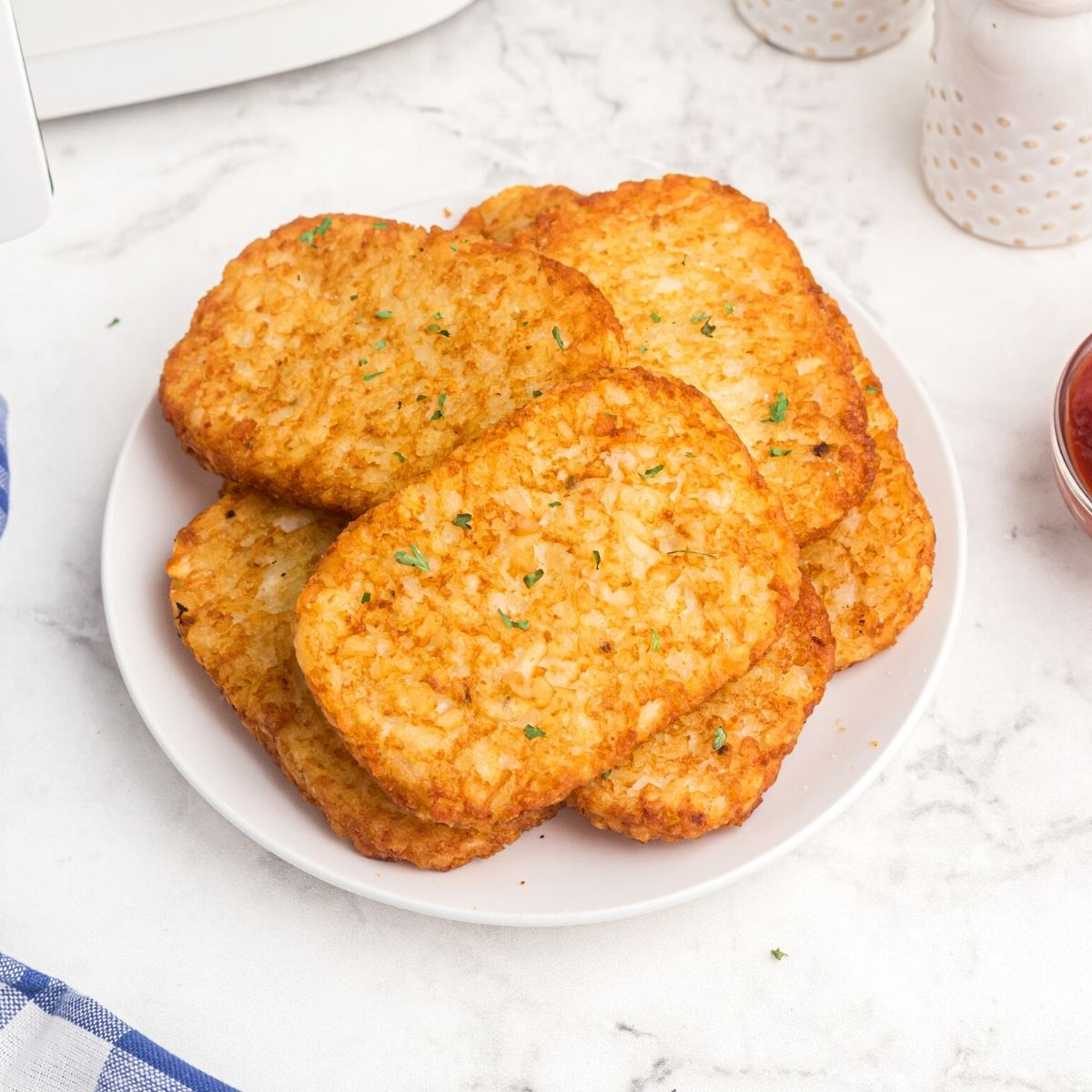 golden hash brown patties on a white plate, served with a side of ketchup.