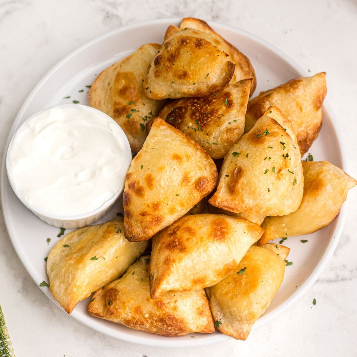 Golden and puffy, cooked pierogies served on a white plate with a side of sour cream.