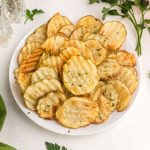 Close up of potato chips on a white plate with fresh parsley garnish on the table.