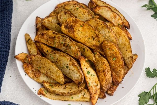 Golden potato wedges cooked and served on a white plate with parsley garnish.