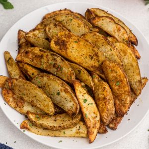golden cooked potato wedges on a white plate showing parsley flakes as a garnish.