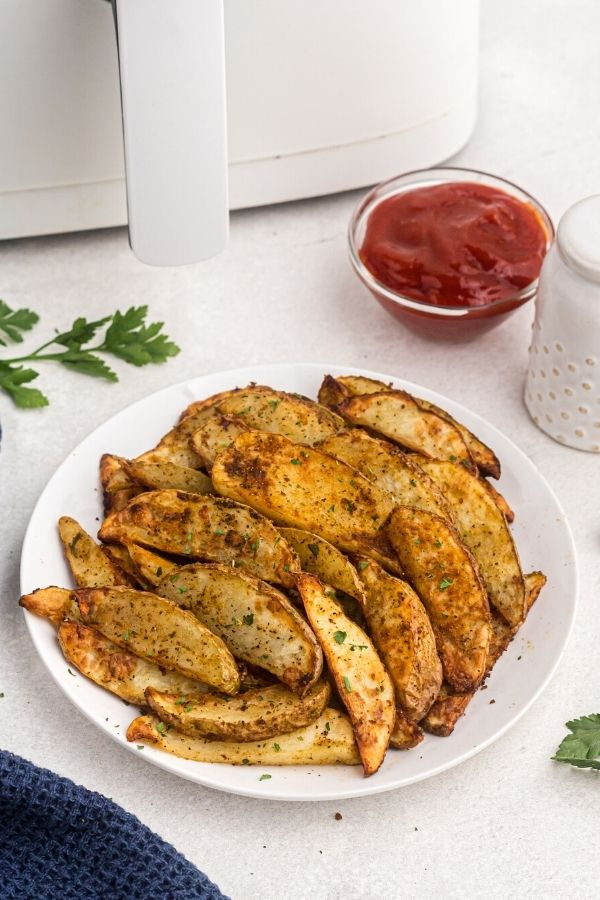 Golden potato wedges seasoned and served on a white plate with parsley garnish on the table.