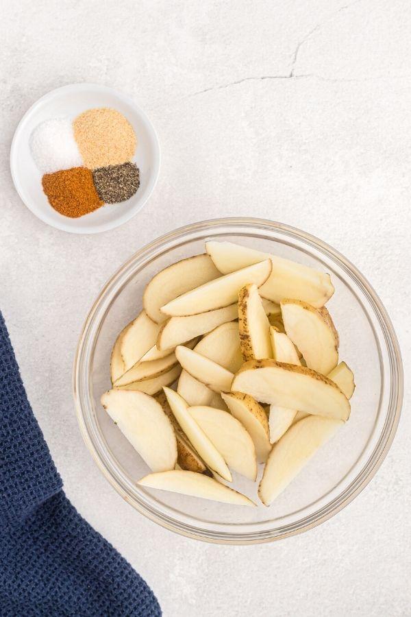 Cut potatoes, seasonings, in bowls before being cooked.