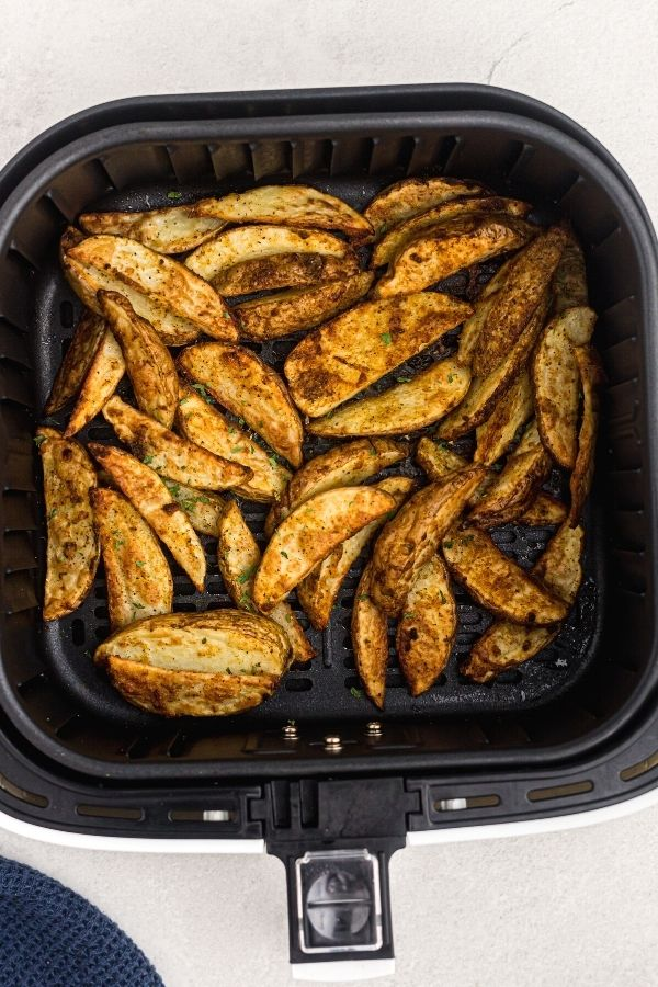 Golden cooked potato wedges, garnished with parsley flakes after being cooked in the air fryer basket.