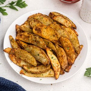 Golden wedge potatoes cooked and seasoned on a white plate.