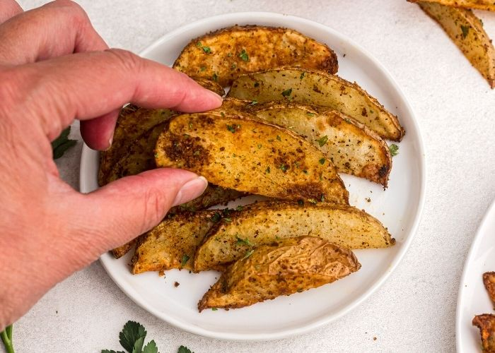 Golden cooked potato wedges served on a small white plate.