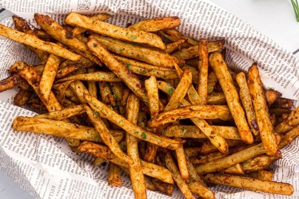 Golden fries, seasoned and stacked in a paper lined basket with parsley flakes garnish.
