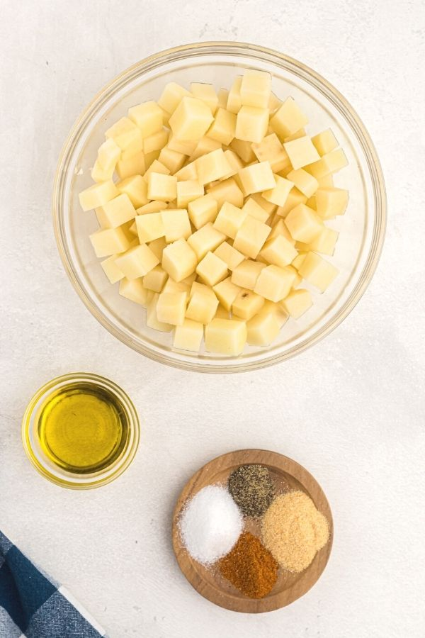 Ingredients needed for breakfast potatoes. Olive oil, seasonings, and cubed potatoes, uncooked.