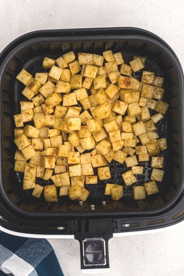 Soaked and seasoned cubes of potatoes, in an air fryer basket. Uncooked.