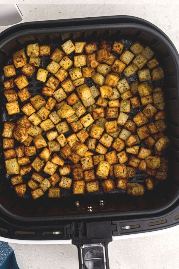 Golden, seasoned cubes of potatoes, in an air fryer basket after being cooked.