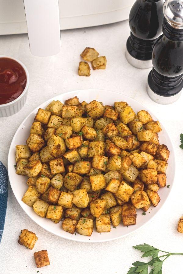 Golden bites of breakfast potato on a white plate.