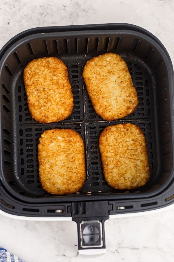 Hash brown patties in the air fryer basket after being cooked. golden and crispy.