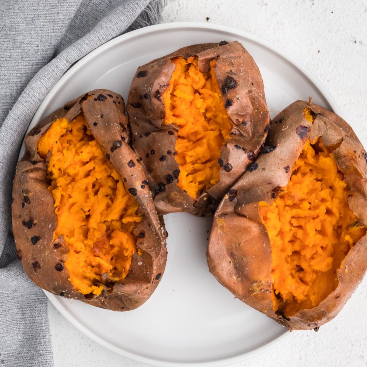 Overhead photo of sweet potatoes on a white plate that were made using an air fryer.