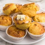 Close up of cornbread muffins with top muffin covered in melting butter.