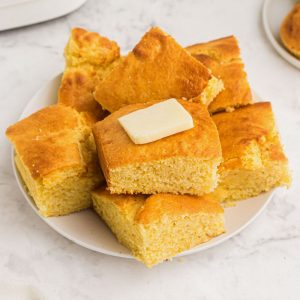 Cornbread on a white plate with butter on top