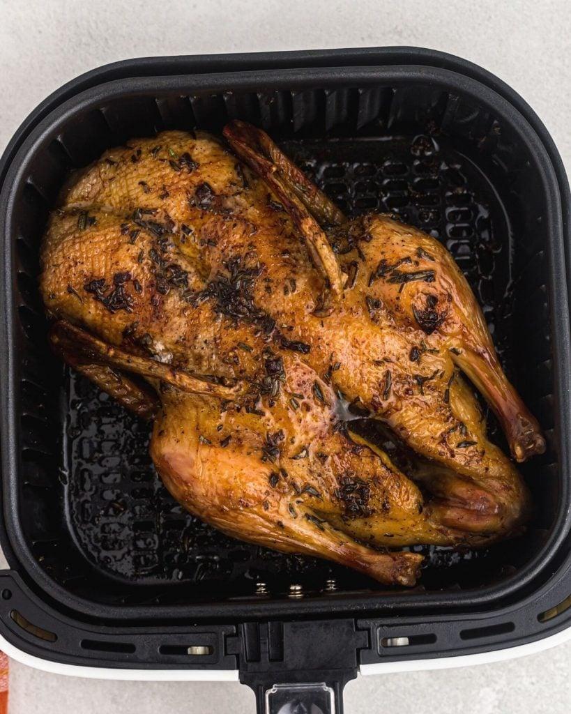 Juicy golden cooked duck in the air fryer basket.