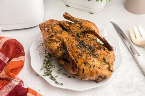 Golden and juicy full roasted duck in front of the air fryer, garnished and on a white marble table.
