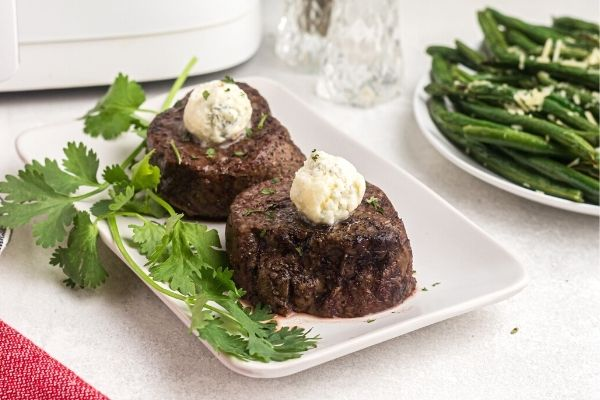 Herb covered filet mignon on a white plate served with parsley and green beans in the background.