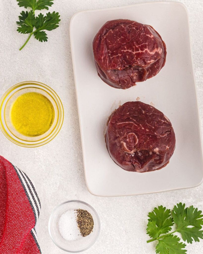 Ingredients to make filet mignon in the air fryer, filets, salt, pepper, olive oil, on a white marble countertop.