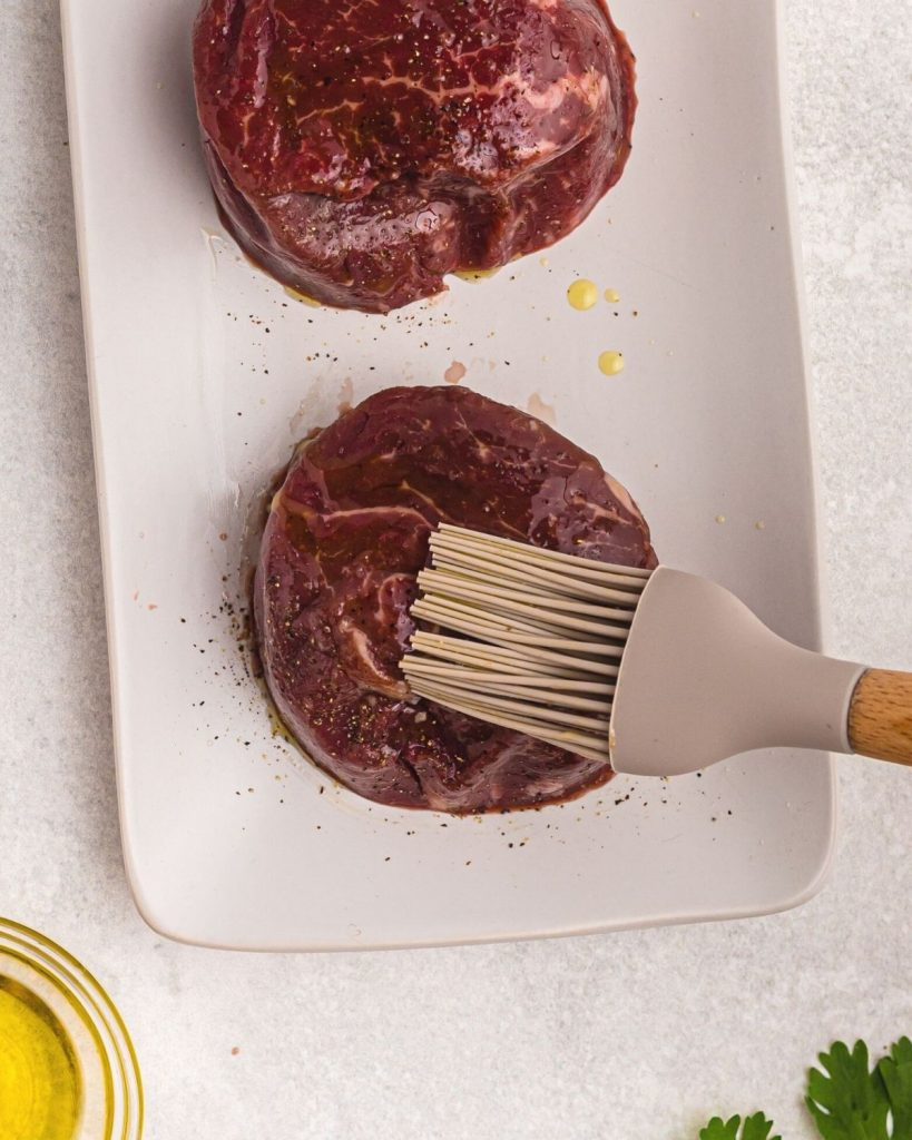 Close up photo showing brush putting oil on filets and then seasoning with salt and pepper.
