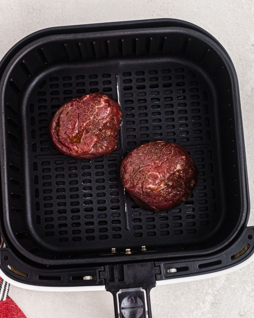 Two red uncooked raw filets in an air fryer basket before being cooked.