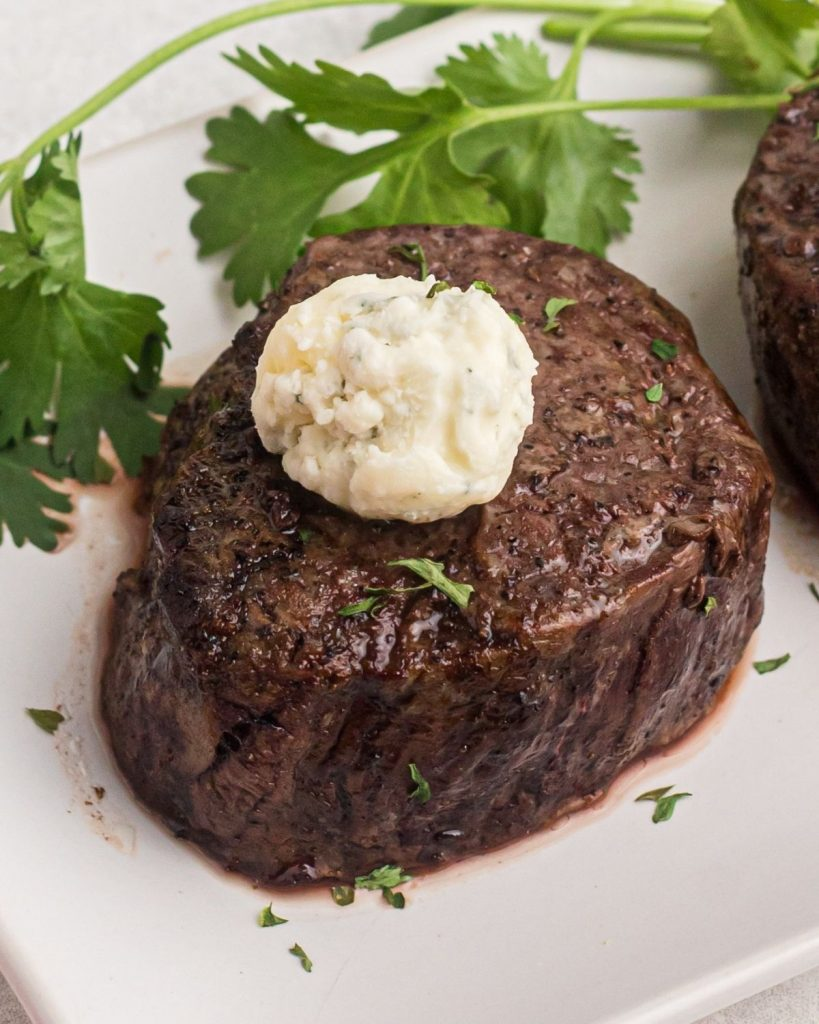 Close up photo of cooked, juicy filet topped with blue cheese butter.