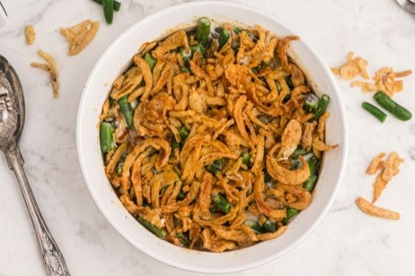 Golden fried onions on top of green bean casserole in a white pyrex dish.