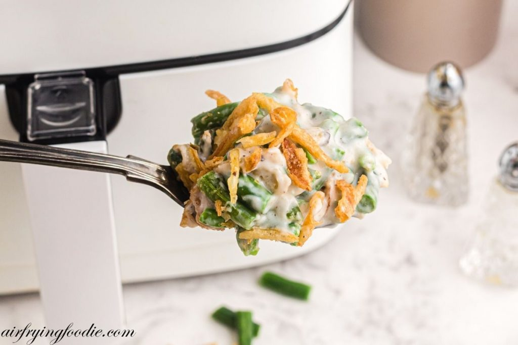 Spoonful of green bean casserole being scooped out of dish in front of air fryer.