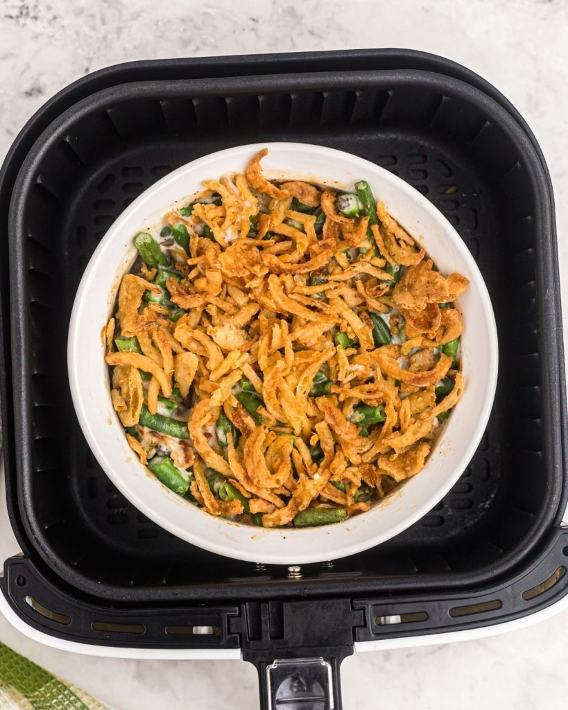 Green bean casserole cooked and golden in the air fryer basket.