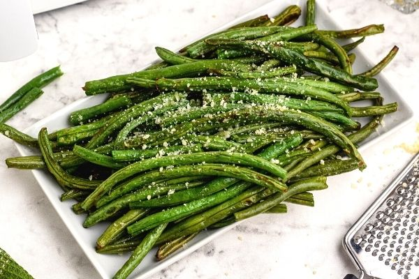 Cooked green beans with grated parmesan on top. Served on a white plate.