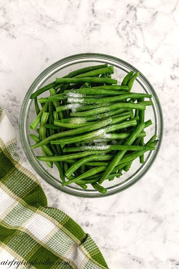 Green beans in a large bowl with olive oil and salt on top before being mixed in.