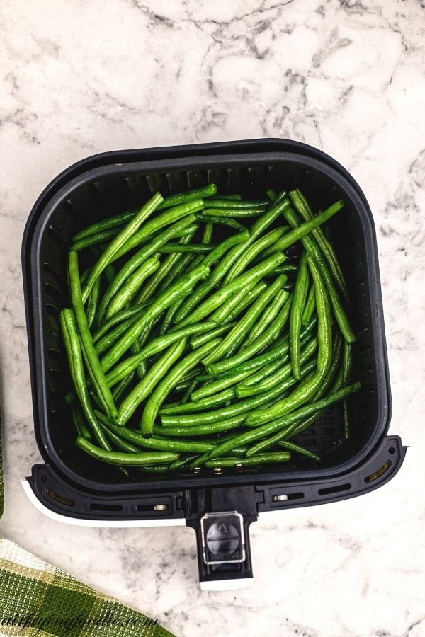uncooked green beans in the air fryer basket before being cooked.