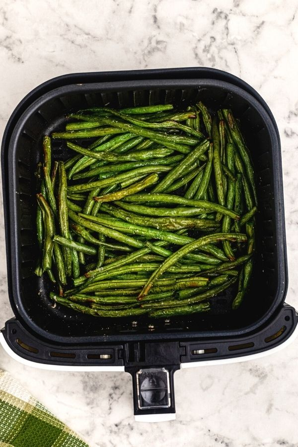 Cooked green beans in an air fryer basket after being cooked.