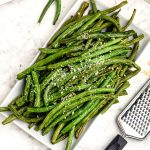 Green beans cooked on a white plate, grated with parmesan cheese.