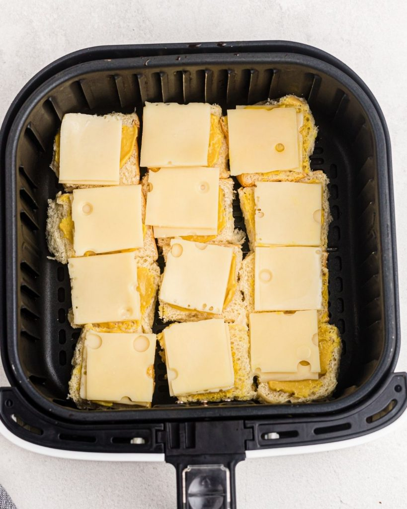 Bottom half of rolls in the air fryer basket topped with mustard and cheese.