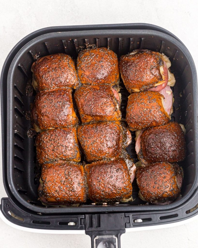 Rolls in the air fryer basket, after being heated in the air fryer.