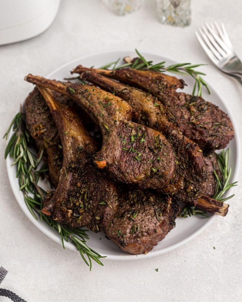Plate of juicy cooked and seasoned chops on a white plate garnished with rosemary.