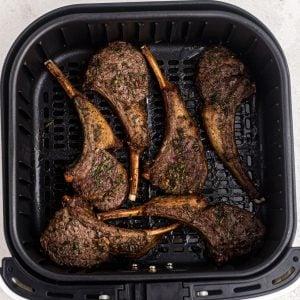 Overhead shot of 6 lamb chops cooked in an air fryer basket, seasoned and juicy.