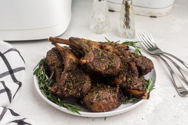 Brown juicy lamb chops cooked and stacked on a white plate and garnished with a sprig of rosemary