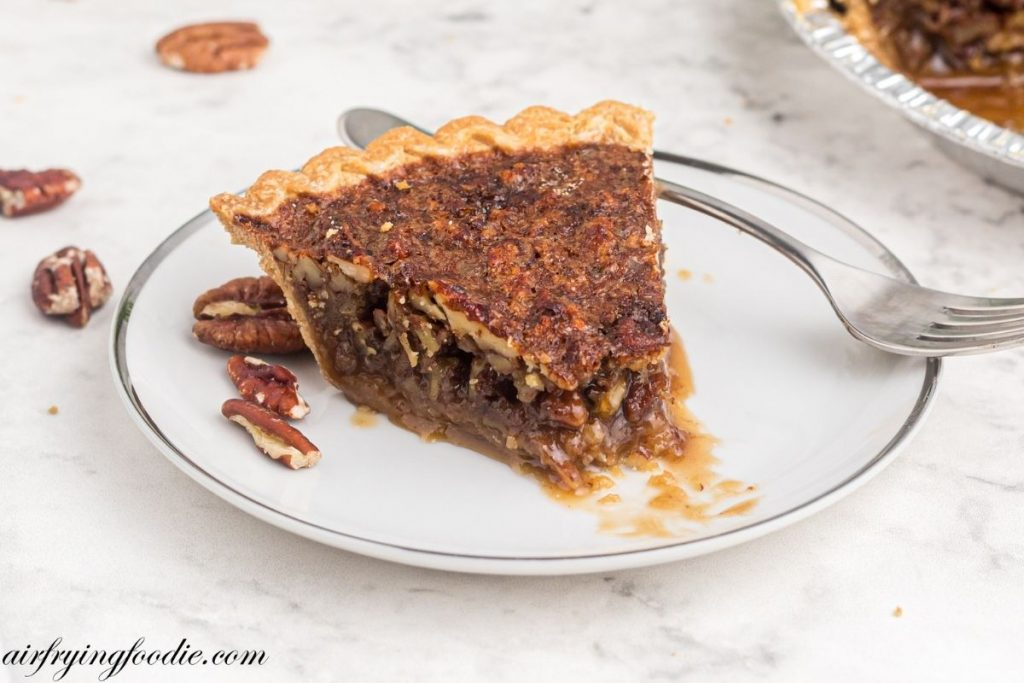 Slice of pecan pie with bite taken out of piece on a white plate.