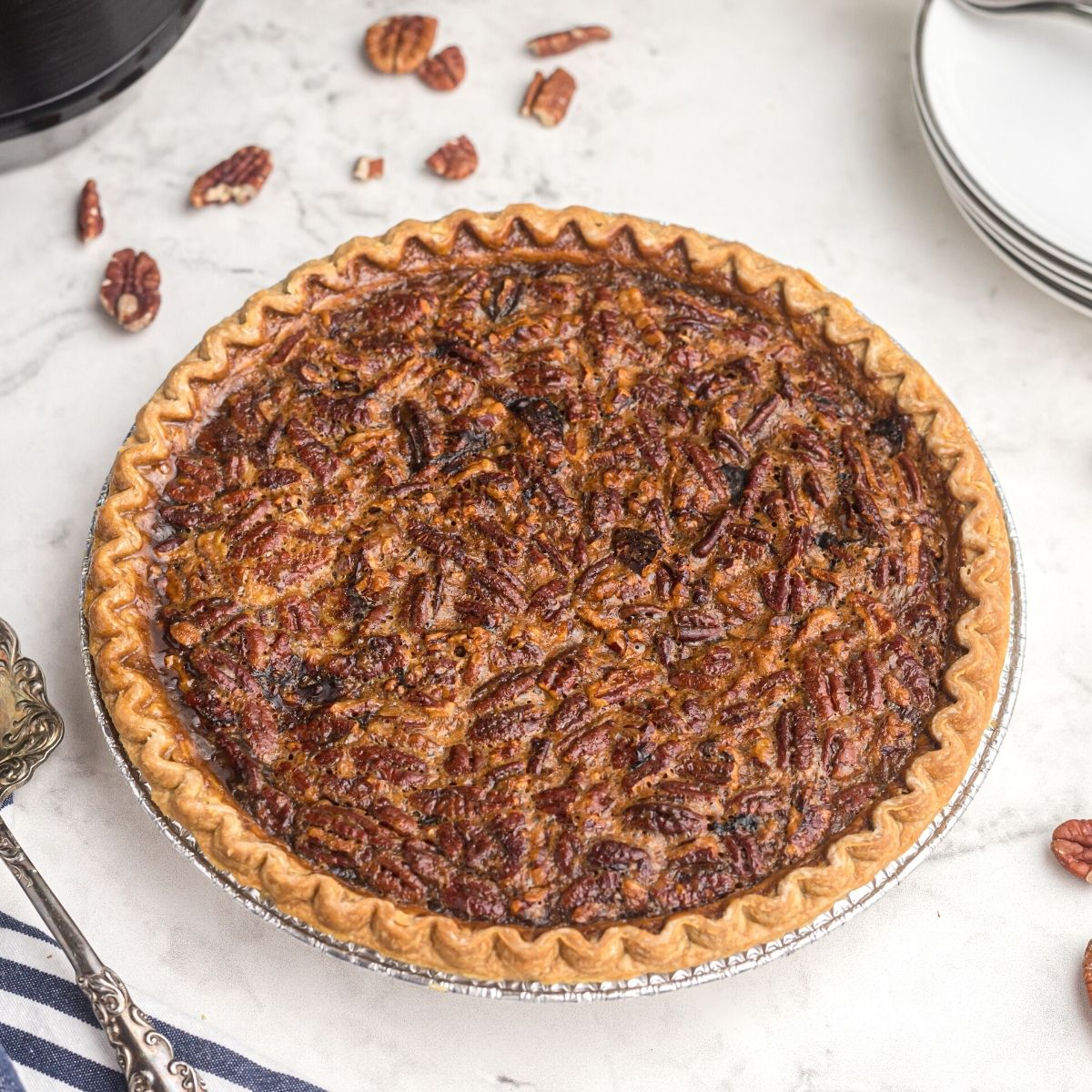 Golden pecan pie on a white marble table with scattered pecans around the pie plate.