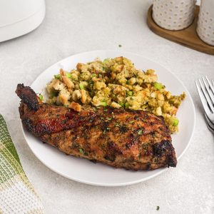 Juicy brown cooked pork tenderloin served on a white plate with a side of stuffing.