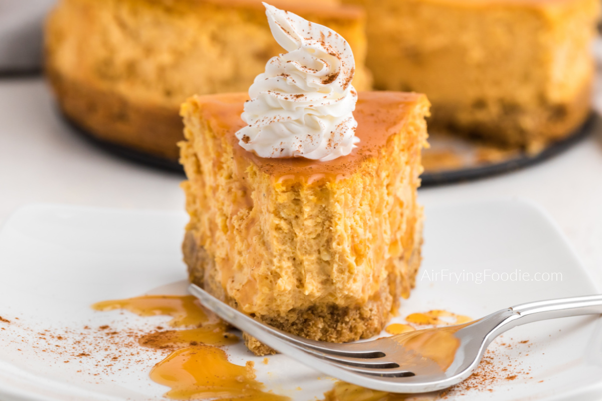 Bite shot of air fryer pumpkin cheesecake with caramel, icing, and a dusting of cinnamon.