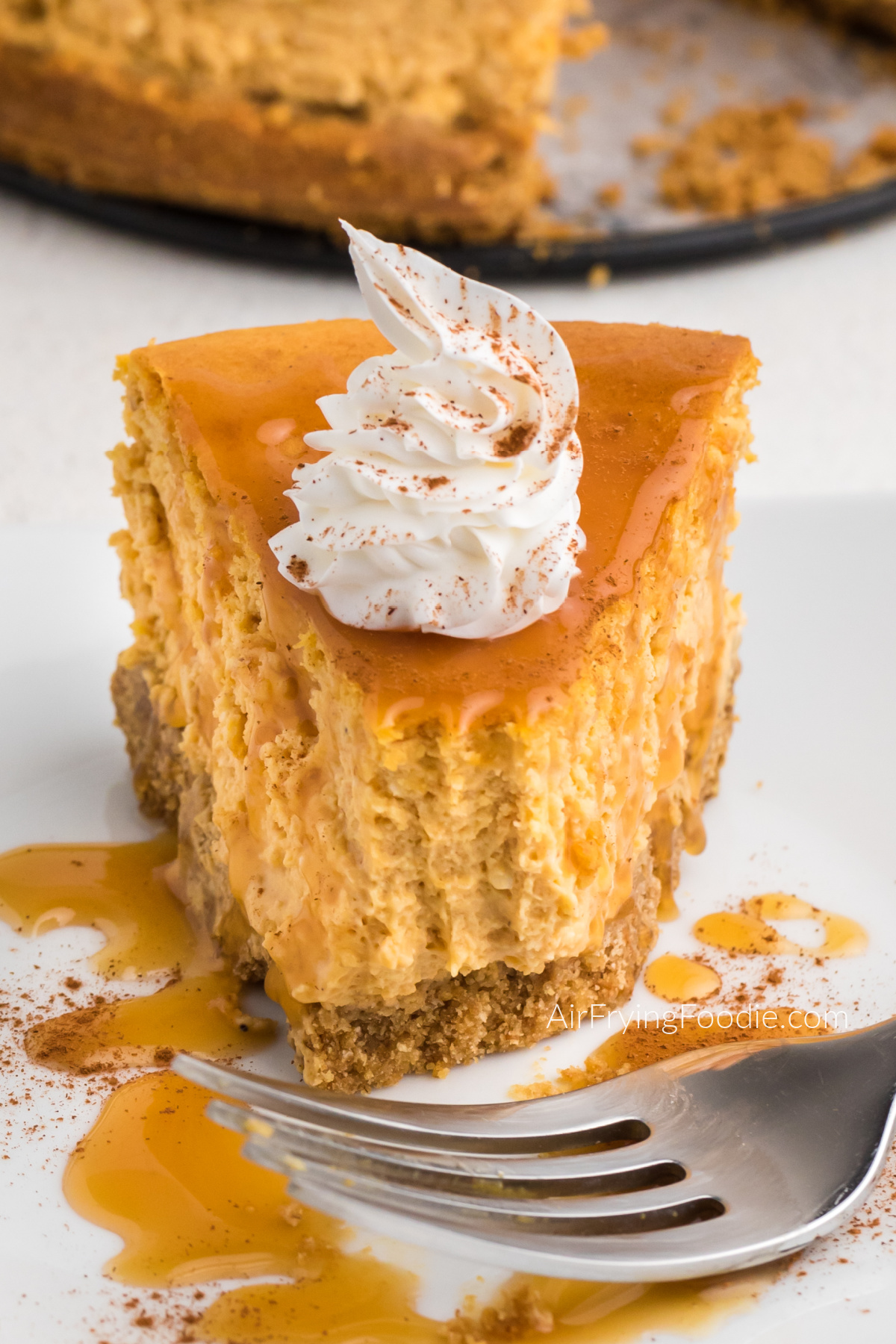Slice of air fryer pumpkin cheesecake on a plate with a bite missing.
