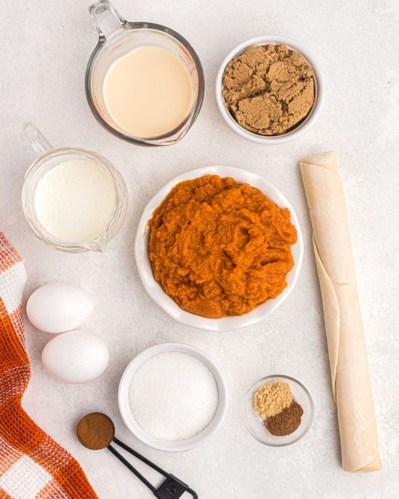 Ingredients needed to make pumpkin pie laying on a white marble table.