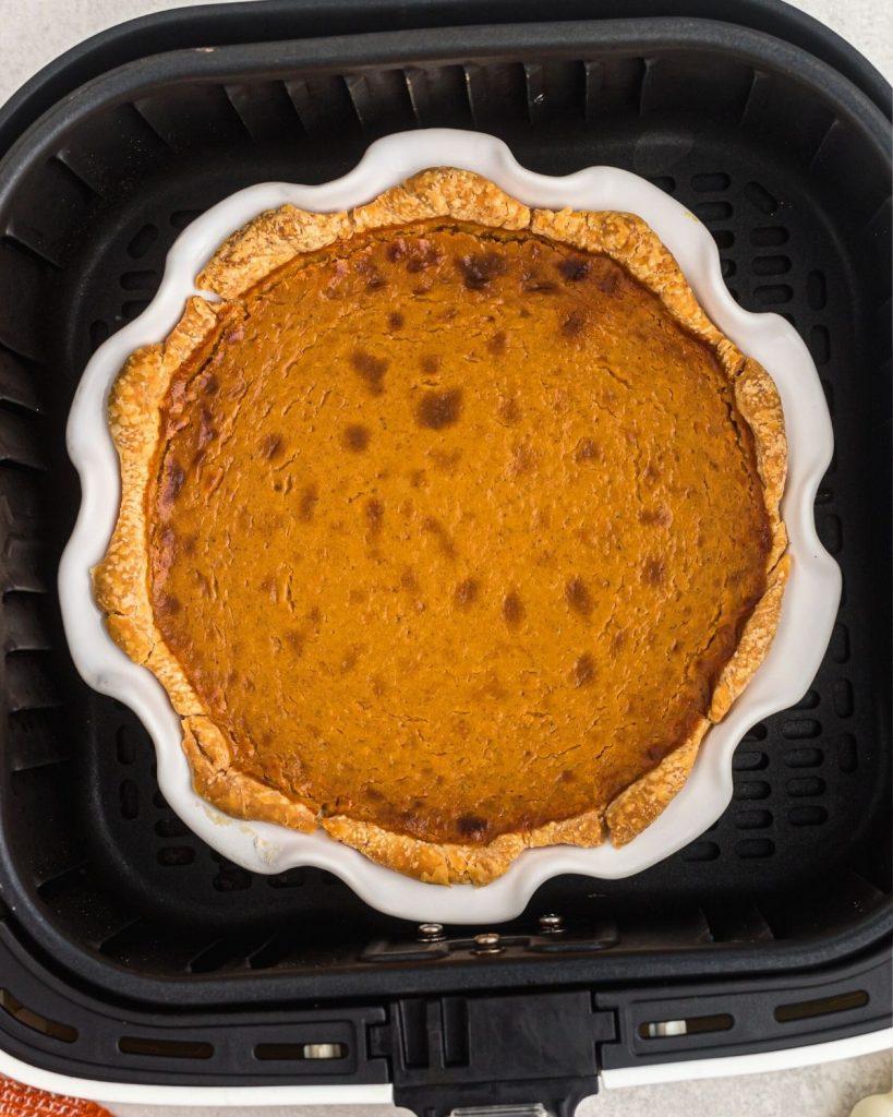 Baked pumpkin pie in a white pie plate in an air fryer basket.