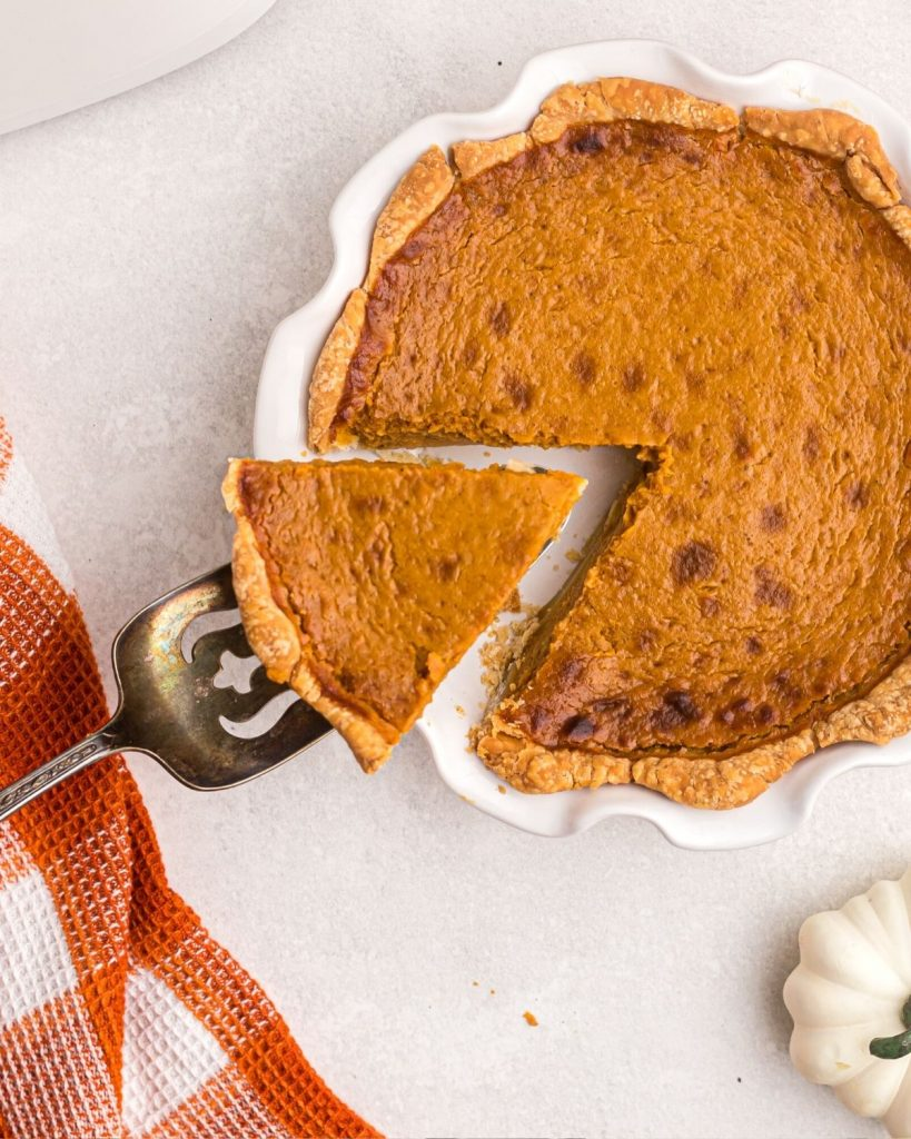 Cooked pumpkin pie with a slice being lifted on an antique spatula.