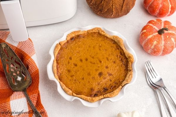Golden pumpkin pie baked in a white pie plate with spatula and forks next to the pie.
