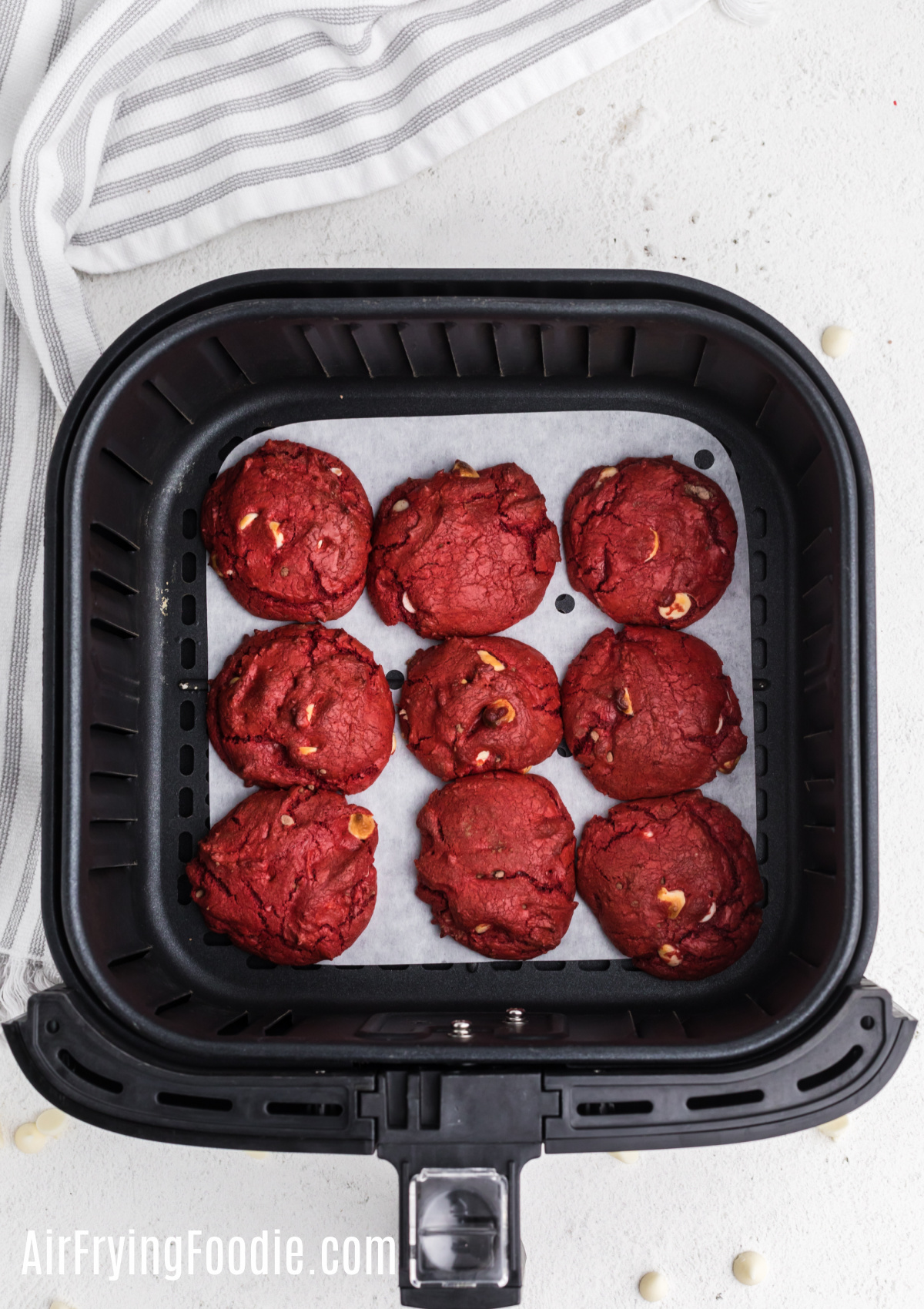 Red Velvet Cake Mix cookies in the air fryer basket on top of parchment paper.